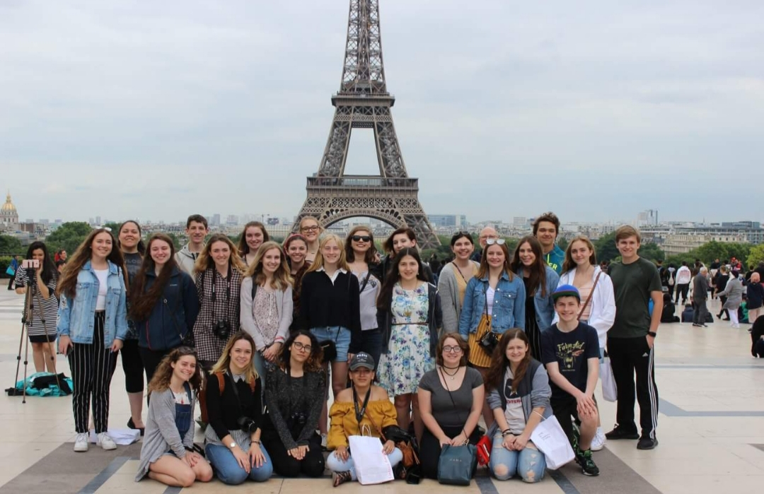 The students all stand in front of the Eiffel Tower. The tower is one of the most the most famous architectural icons of the world and is easily recognized by many people.