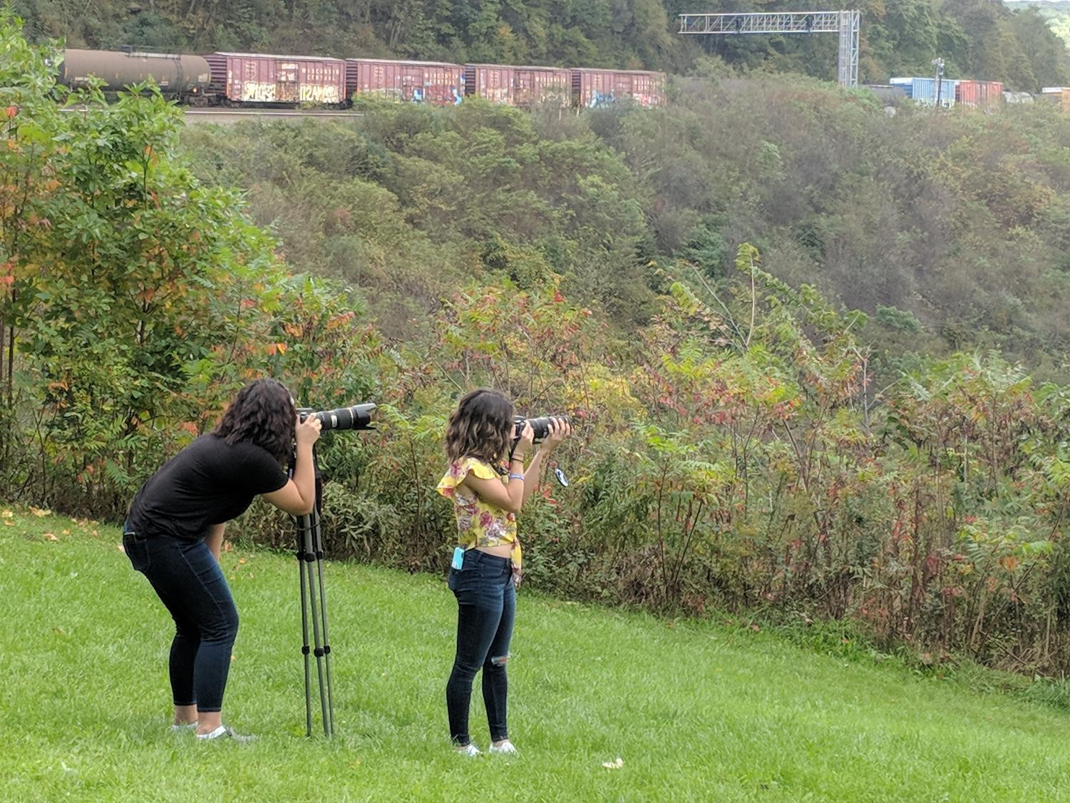 Waiting patiently Seniors Samatha Rolls and Kierra Moist capture photos as a train travels around the Horseshoe Curve.  Students rode the incline to the top and had a long wait for the train.