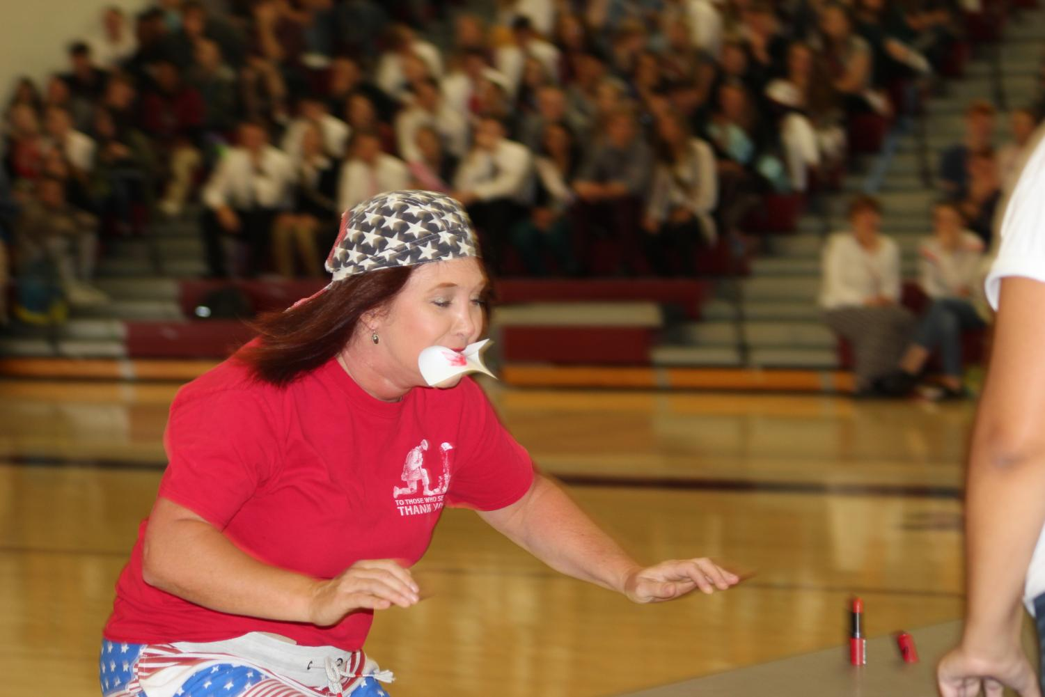Pucker up Carolyn Kline races to the finish with a playing card in her mouth during the assembly. Two teacher teams competed against each other using games the homecoming candidates would play the next week.
