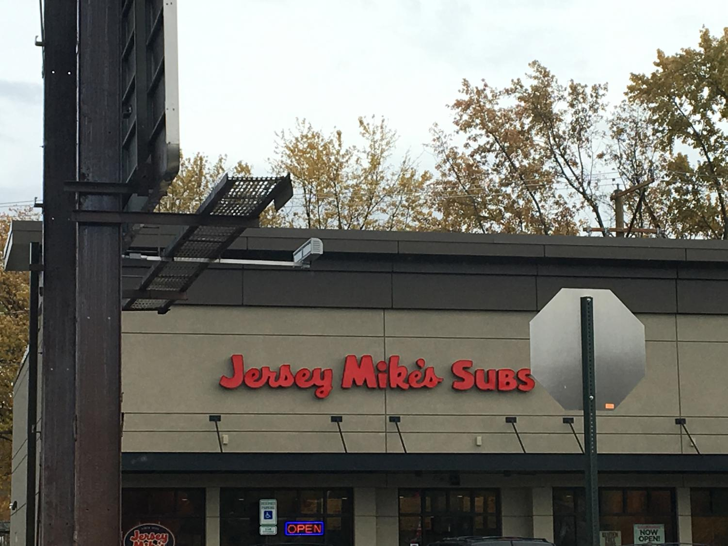 The outside of Jersey Mike's provides a lot of parking for people to come in and get a sub. The outside features a bright and colorful sign that will appeal the attention from drivers who pass by. The outside is includes entertaining music, cool and different wall art.