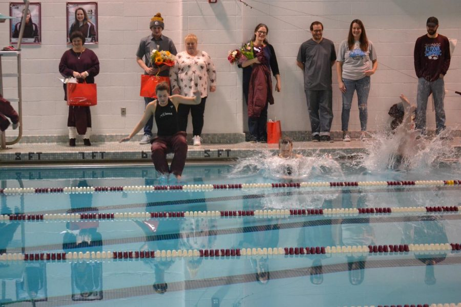The seniors jump into the pool as their parents and teammates watch.