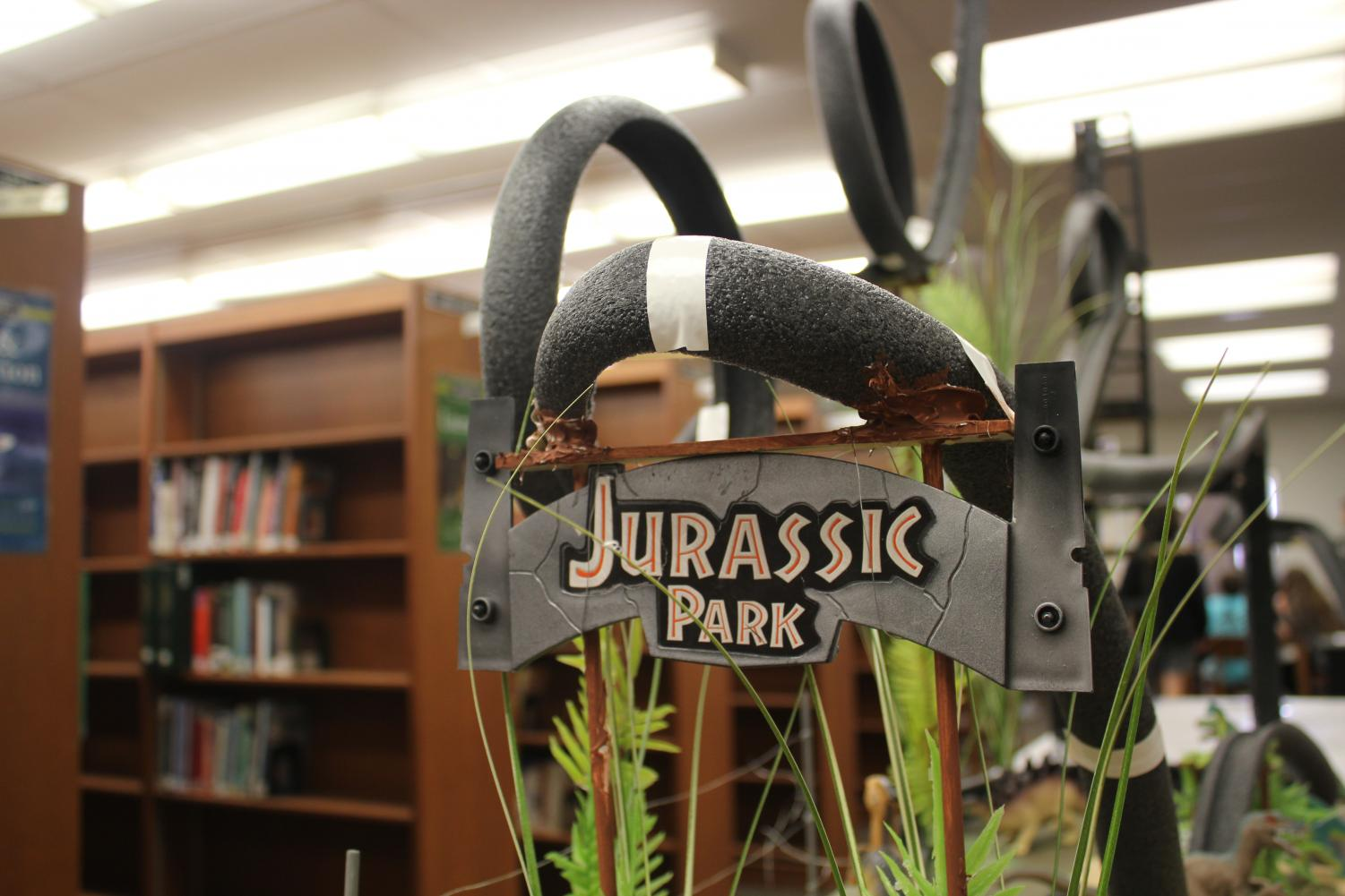 The Jurassic Park sign hangs from the track of an academic physics roller coaster in the library. The coaster had many loops, curves, and inclines included, as students were graded on the features of their coaster.