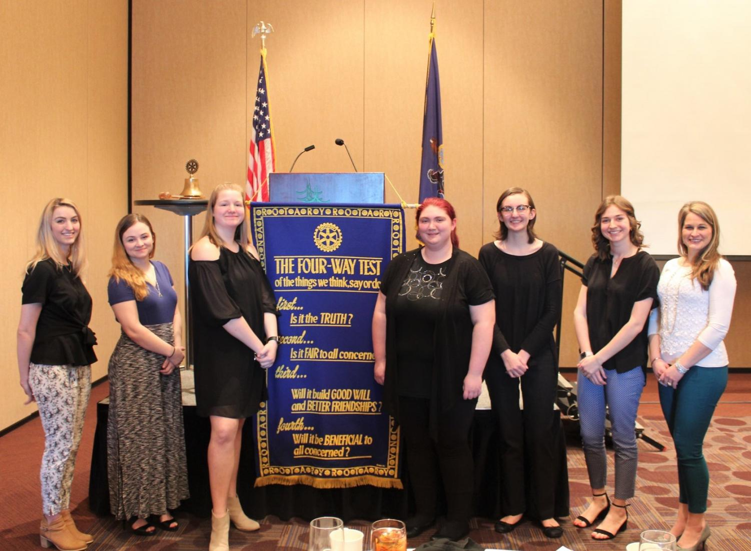 Heather Tippett-Wertz along with the five competitors and student teacher, Carly Schankowitz stand for a picture at the end of the contest.  Also pictured is the list of 4-Way tests that gave directions and set a foundations for addressing the topics presented.