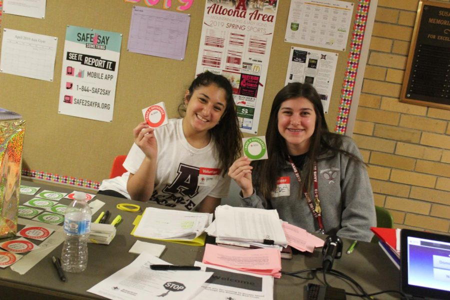Grab+A+Sticker%21+Junior+Gianna+Marasco+and+senior+Zoe+Wilson+hold+up+red+and+green+stickers+for+the+students.+These+stickers+were+for+first+time+blood+donors+and+previous+blood+donors.