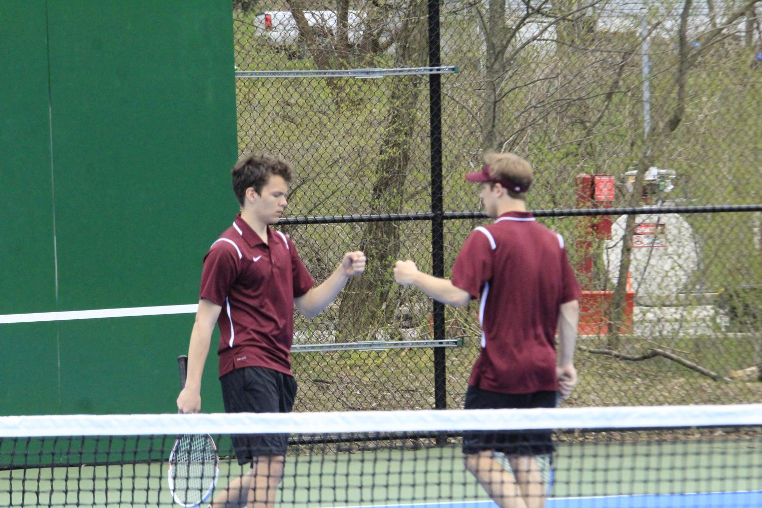Senior Tyler Robinson and Junior Colby Bickel first bump after winning a doubles set against Hollidaysburg .