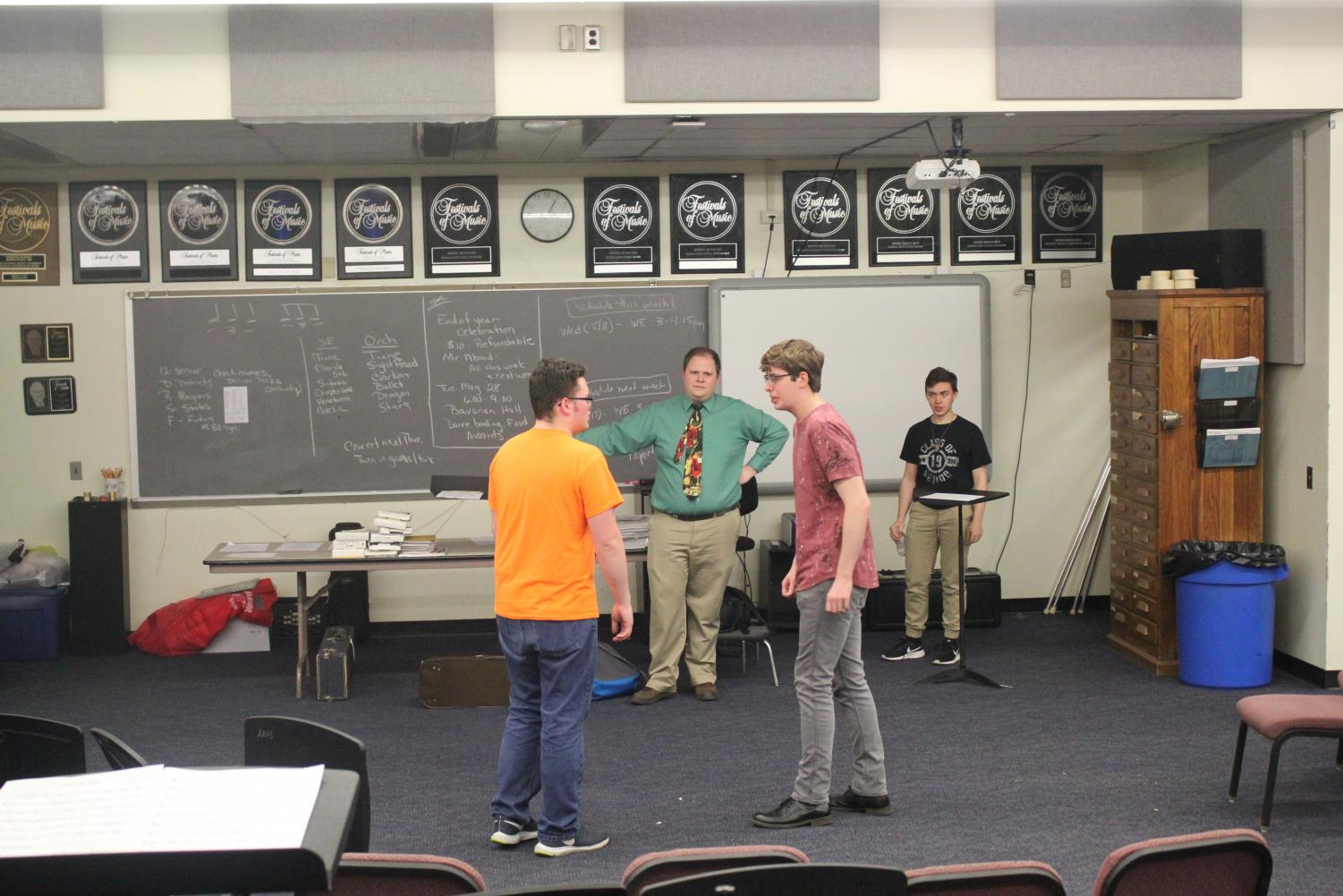 Practice makes perfect. Junior Jarrett Hann and senior Christian Howard prepare for the Isaacs by practicing one of their musical numbers from the play. Drama adviser and play director Ben Cossitor observes them as he adds notes to help with the upcoming performance.