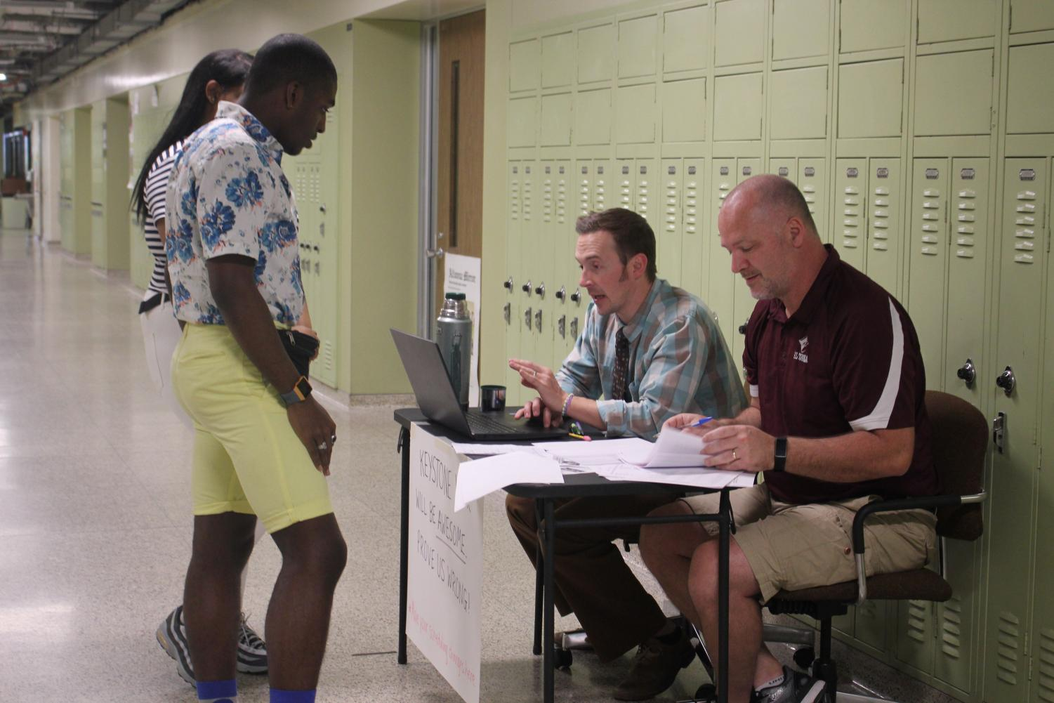 Can I change this? Junior Ahmil Bey Johnsin and Senior Al-Ziona Smith ask James Krug and Tom Palfey to change their activities. Palfey and Krug sat in the halls to make changes to students itineraries.