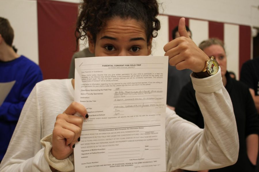Junior Eryka Moss, holds the permission form needed to take home and return.
