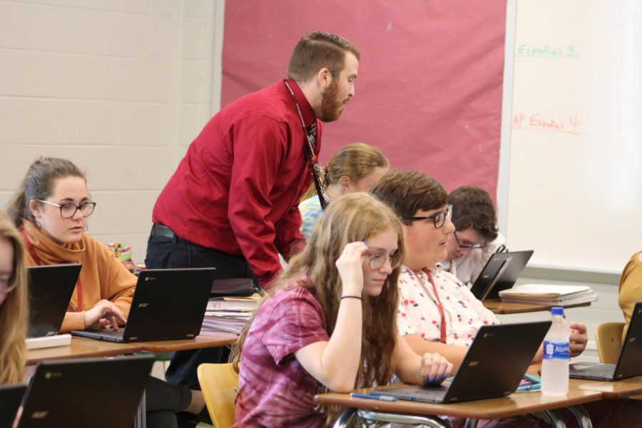 Help  AP Spanish teacher Dane Leone helps a group with ideas they could use during their presentation. Leone also discussed certain ways they could teach it during their presentation.