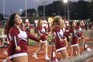 During last year's football season, the cheerleaders perform a routine on the side of the field. The cheerleaders go to both the away and home games.