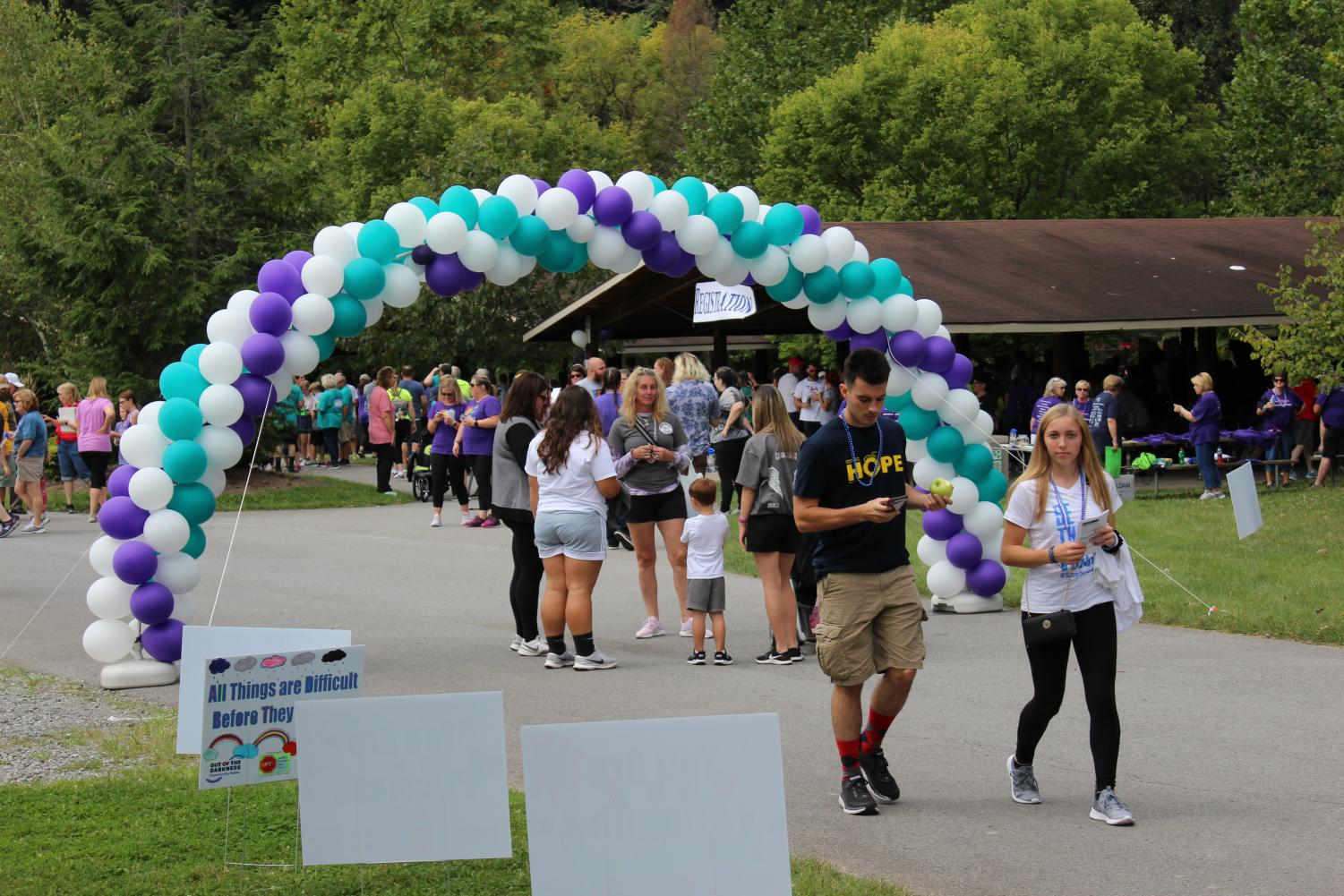 #rememberingthosewelove. Walkers gather under the balloon entrance to begin the suicide prevention walk.