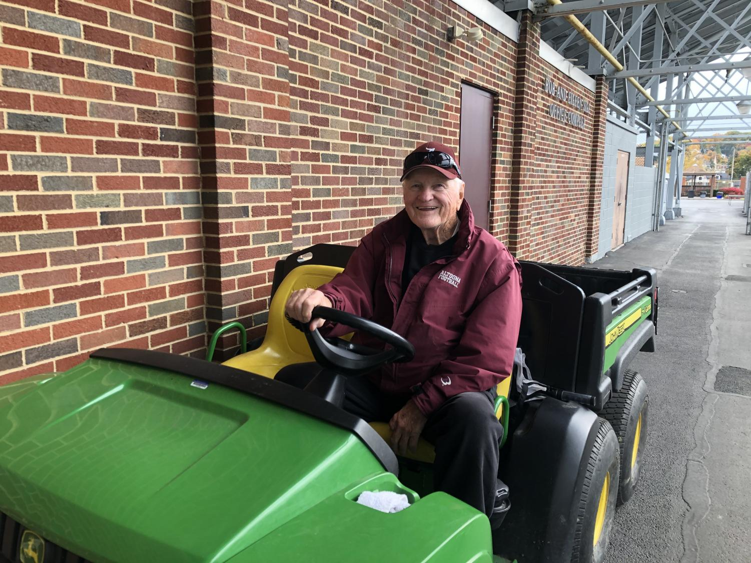 Smile! Sammy Miller poses in his iconic green Gator. Miller rides his cart to help set up practices.