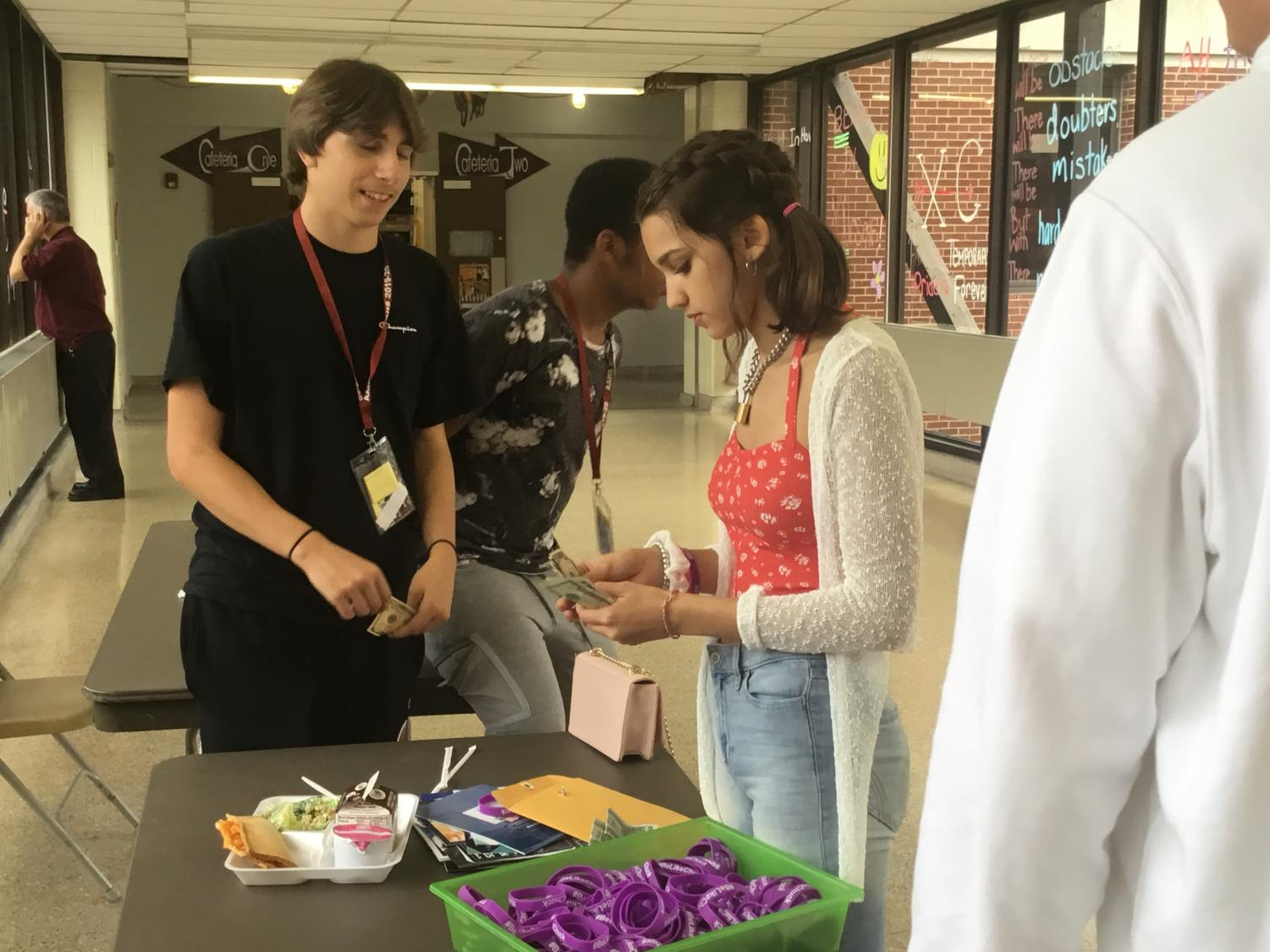 Buy one! Junior Mychenze Alberts sold the #BeLikeChuck bracelets on the bridge to a fellow student.  Students bought the bracelets during their respected lunch periods.