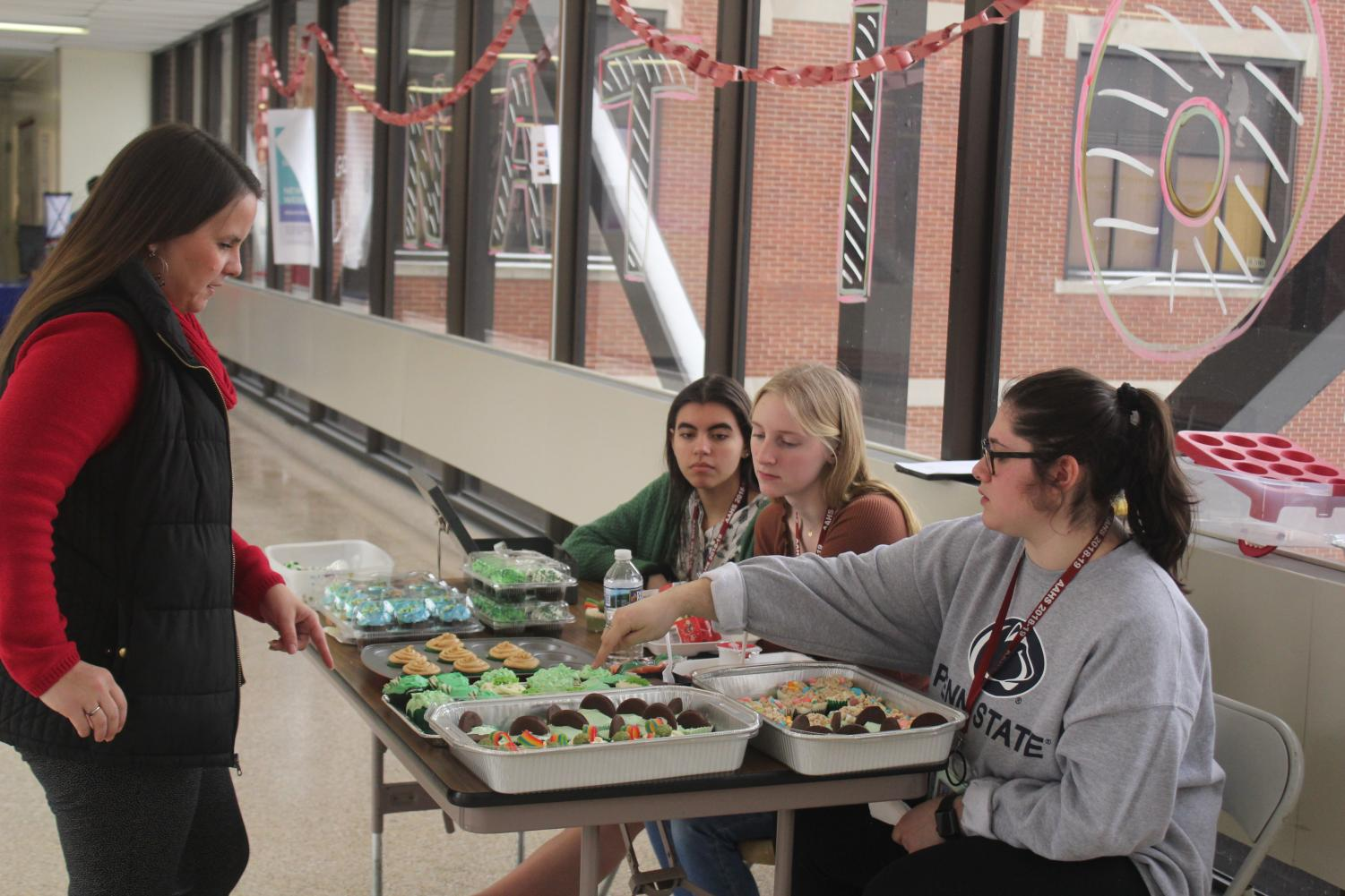 Seniors of last school year, Takera Jones, Bailie Newberry and Reagan Baker sell baked goods on the bridge for Girls' League. They sold their homemade baked goods to Emily Bender.