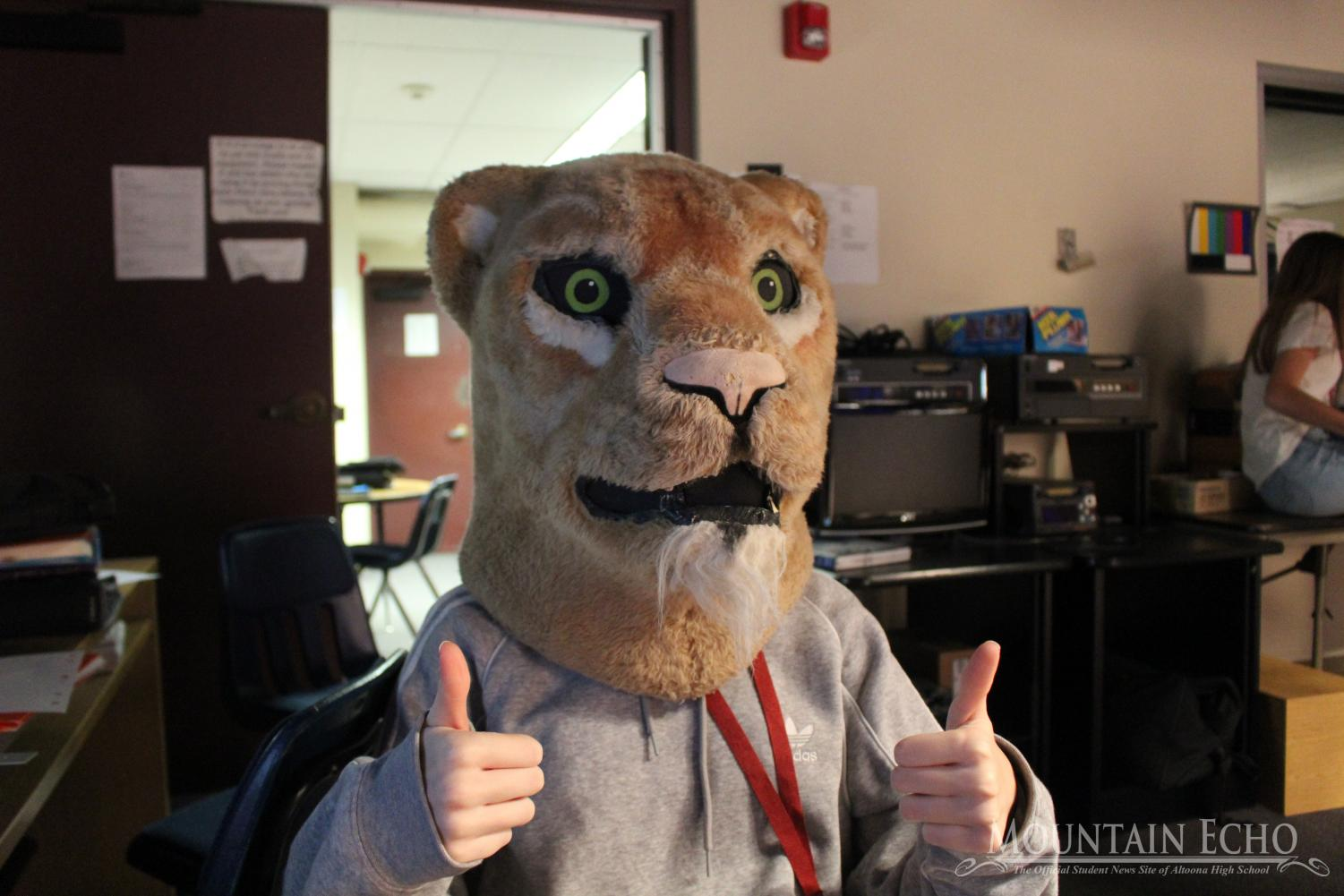 Sophomore Kayla Zeth puts on the Mountain Lion head for giggles during Broadcasting I. Zeth was waiting her turn to do the voice over for the MLTV. In Broadcasting I, students practice for each of the broadcasting positions.