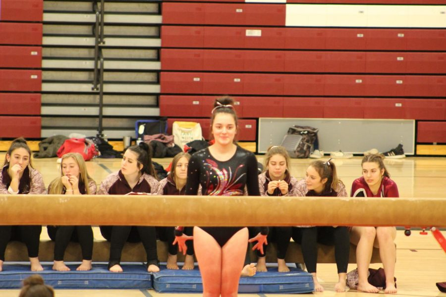 Im Ready Senior Miranda Butterbaugh gets ready to jump the balance beam at the first gymnastics home meet. The gymnastics team participated in their first meet on Dec. 9.