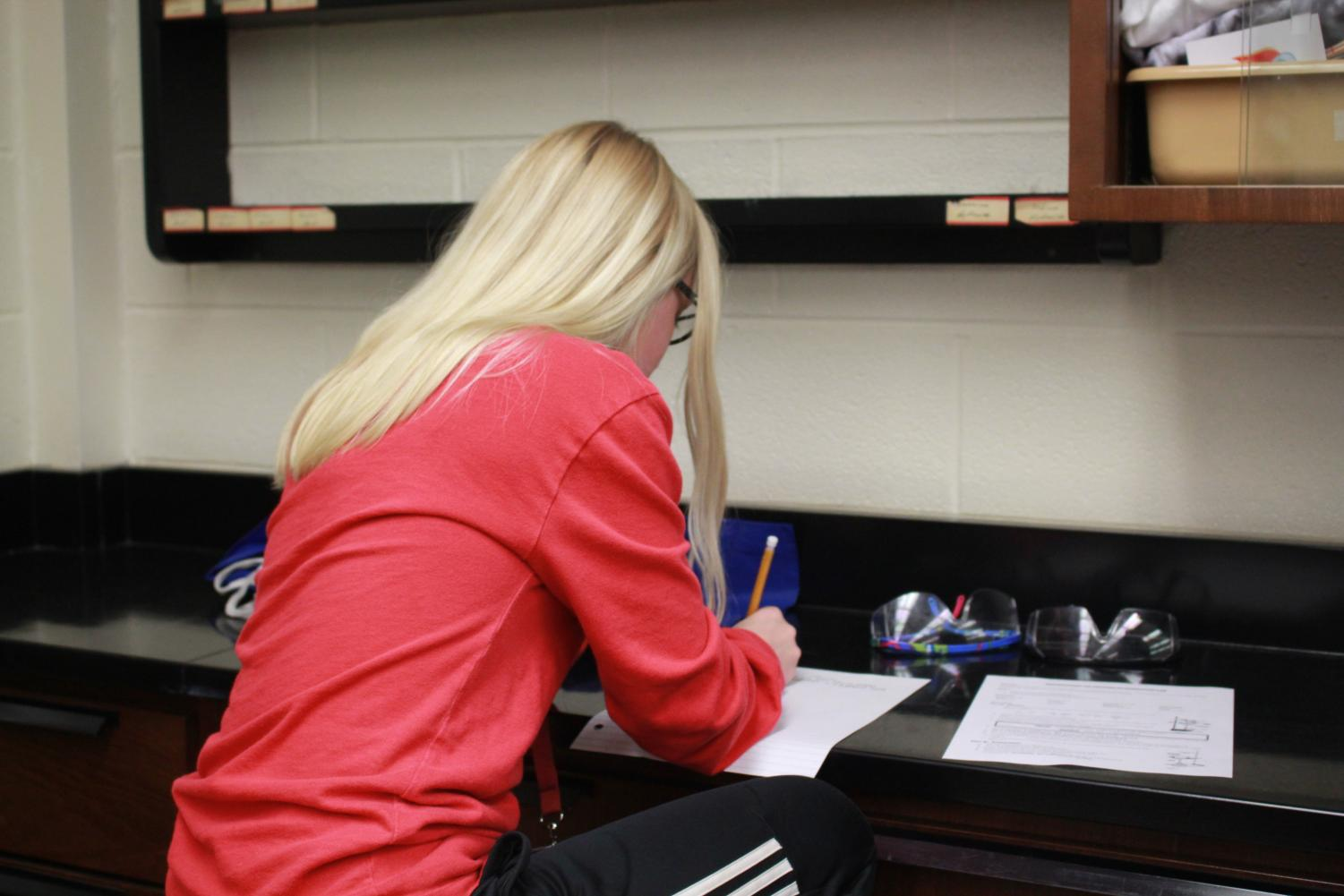 Sophomore Alanna Cunningham works on physics classwork days before the first marking period midterm. During the first midterm, students claimed to have plenty of time to study yet presently, students disagree with the midterm schedule. Many believe midterms should be held back or pushed further due to the eight-day holiday break.