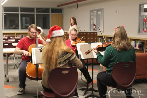 Entertainment for the Kids,  The string quartet entertains the families at the holiday party. The four students played many Christmas songs on their instruments.