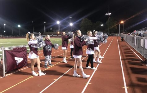 Vallei, pictured on the left, cheers with Sparkle Cheer during halftime at a football game. Sparkle is an all-inclusive cheer squad that Vallei participates in as well.