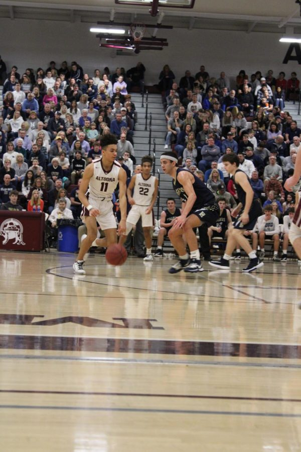 Focus on the Game Senior star boys' basketball player Kennth Futrell dribbles the basketball down the court against Hollidaysburg. Futrell accomplished many goals he set for himself in his high school basketball career.