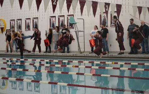 The seniors jump into the pool with their warm-ups on, a tradition for the swim team.