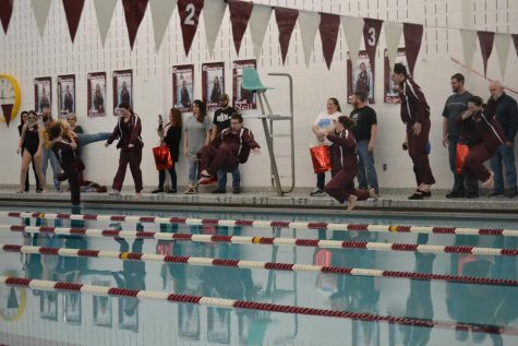 "The seniors jump into the pool with their warm-ups on, a tradition for the swim team.  ""It feels so weird to be leaving after all this time. But, I"