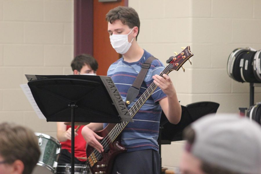 Senior Alex Thaler examines a piece of music and selects the proper finger pattern. Thaler has been playing the electric bass for six years.