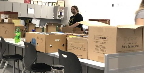 Senior Sonia Yost works to unpack boxes in the new journalism room B130.  Yost works with Wanda Vanish for community service and spent three days helping to get the room ready for students.
