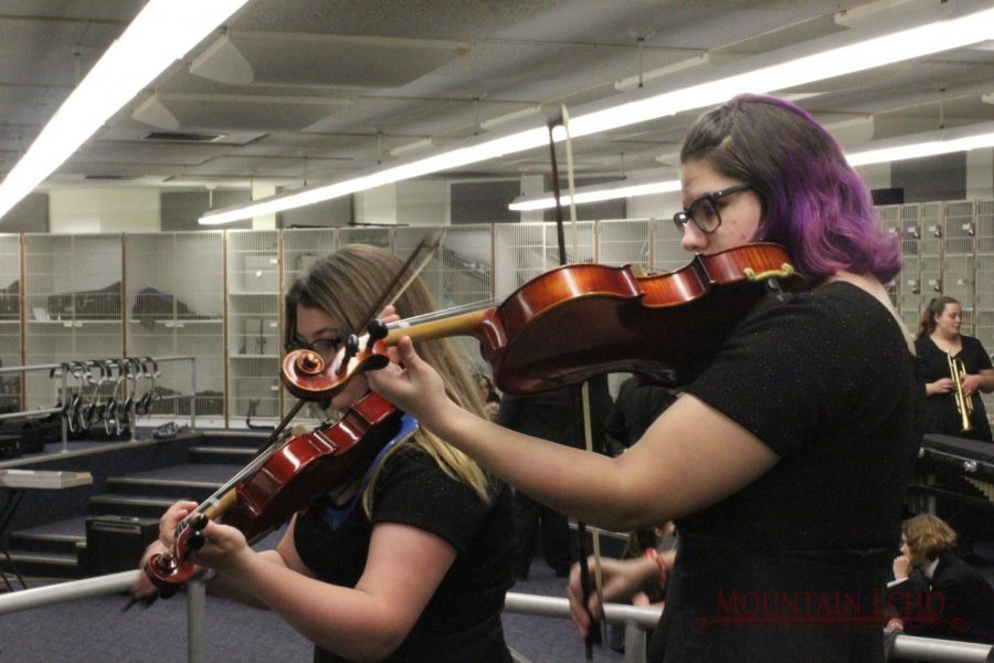 Warm up! Violinists Hannah McGuire and Aeryal Palazzi practice last minute right before they go on stage. They are two of many violinists practicing. (PHOTO TAKEN DURING 2019-2020 SCHOOL YEAR)