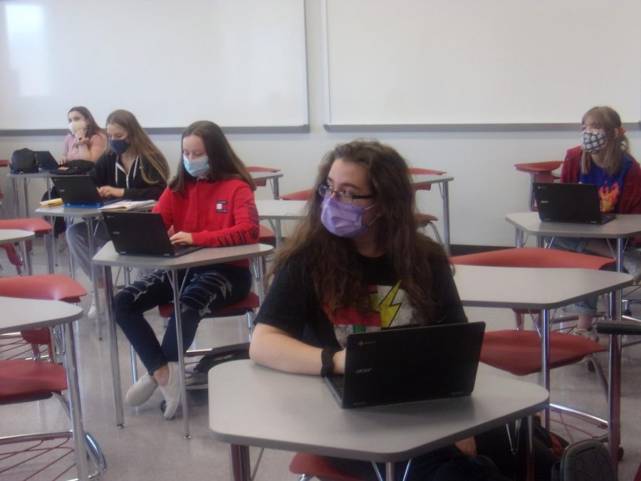 Following guidelines during the school day. During the school's hybrid schedule, students and teachers were required to wear masks and social distance as much as possible. In this history class, students can be seen following these mandatory guidelines. The number of students in classes are significantly less due to the hybrid model.