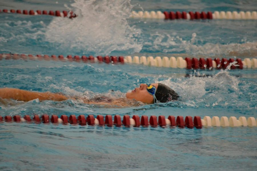 At a 2019 swim meet, then junior Makenna Murphy swims backstroke during the 200 IM.