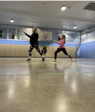 "Twirler Arabella Wilt and Coach Renee Parowski lunge in preparation for the upcoming competition season. ""I'm excited for competitions and I hope that I get the chance to do it with my friends,"" Wilt said."