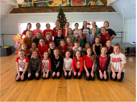 Pictured above is Competition year 2018-2019's annual christmas party. The dancers pose for their group picture before opening presents and eating lunch together.