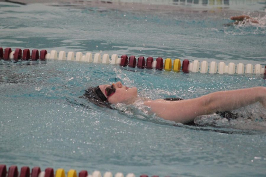 Preparing to pull her arm through the water, sophomore Alexis Fraundorfer swims the backstroke in the 200 individual medley. Fraundorfer placed first in this event and the 100 butterfly, giving the team 12 points.