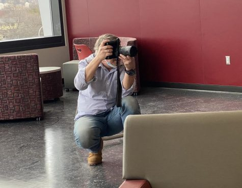 Say Cheese! Tim Boyles crouches to take a students picture. Boyles has been offering the opportunity to get free professional portraits taken for two years.