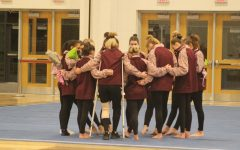 During the girls' gymnastics senior night, they gather around in a circle.