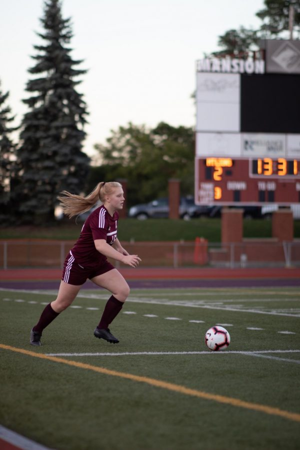Serve! Junior Becca Dull goes to pass the ball. Girls soccer is only one of the many sports that use Mansion Park.