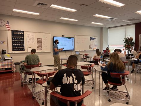 Help please! Student teacher Joseph Tanguay assists both students in the classroom and quarantined in Kathryn Chestneys eighth period math class. Chestney and Tanguay worked together to assure they could help both groups of students as much as they needed.
