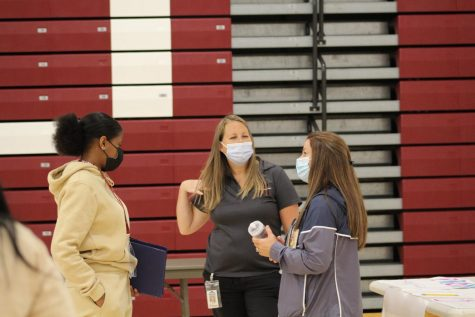 Masking Up Physical education teachers Julie Schmoke and Megan Yingling talk with a student during the first day of school activity fair.  Masks were optional for students at the start of the school year but are now mandatory unless a mask exemption is submitted to administration.