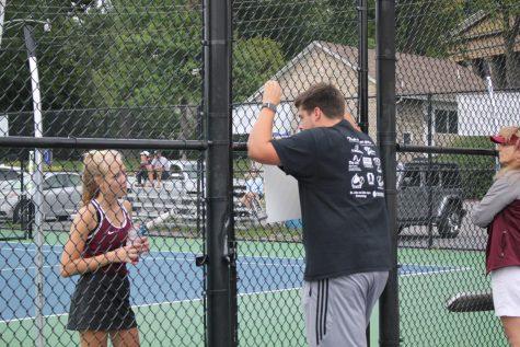 Listen up!  Jake Colledge coaches freshman Kendall Gates at their tennis match. Colledge led the team as a first year head tennis coach