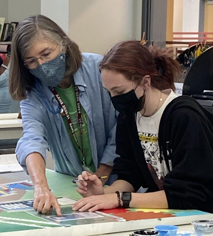 """Teamwork! Deb Dunnell assists sophomore Meleah Lang as she paints. She claimed that she loved working with Altoona students. """"The students in these two art classes are great, theyre excited about being part of the mural, and theyre aware its a very popular part of the school,"""" Dunnell said."""