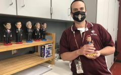 Wobble Social studies teacher Shane McBurney leans on his counter, posing with his bobbleheads and Rosie the Riveter. McBurney got his first bobblehead during his first year of teaching.